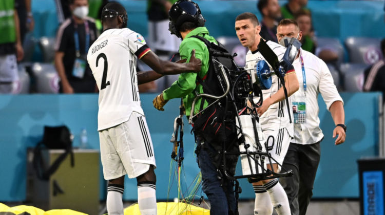 VIDEO Înainte de meciul Germania-Franța, un activist a aterizat cu parapanta pe teren. A rănit spectatori!